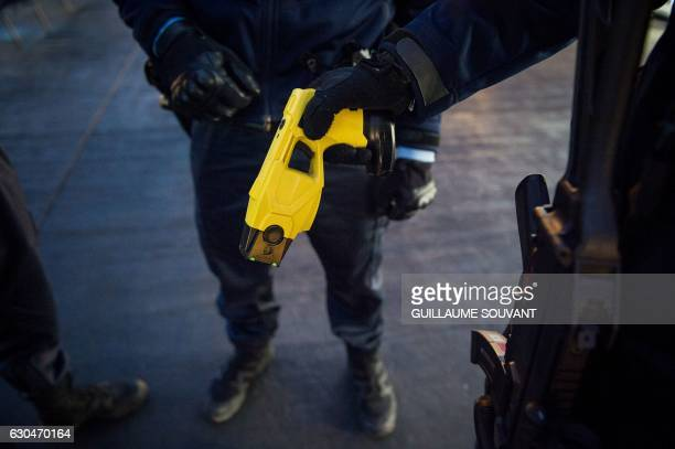 A French gendarme holds a taser as he patrols at the Christmas market in Tours central France on December 23 2016 Security was beefed up at Christmas...