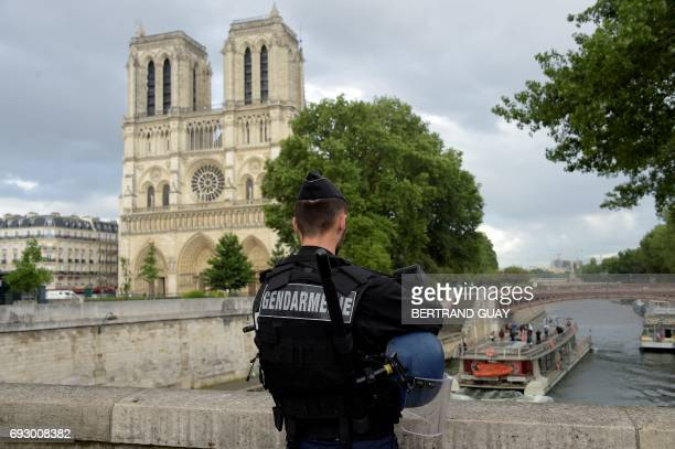 A French gendarme holds his helmet as he stands on a bridge near the entrance of NotreDame cathedral in Paris on June 6 2017 Antiterrorist...