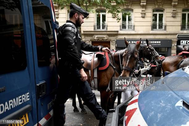 French gendarme looks at his watch next to horses of the French national guard before the start of the Bastille Day military parade down the...