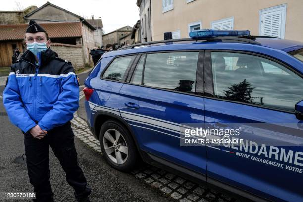 French Gendarme looks on next to a Gendarmerie car in Saint-Just, central France on December 23 after three gendarmes were killed and a fourth...