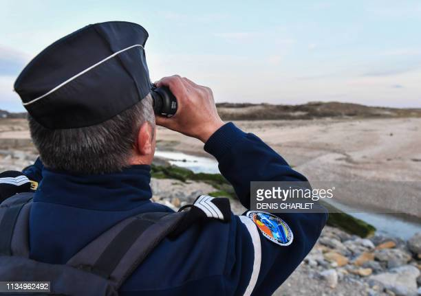 French Gendarme looks through a pair of binoculars during a patrol of the beaches at Tardinghen near the northern port city of Calais on April 4,...