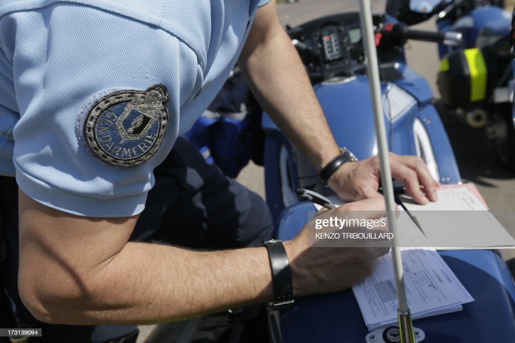 A French gendarme Motorcyclist arrests a driver on July 6, 2013, on the highway A6-A31 in Beaune, eastern France on the first day of major departures for the summer holiday.