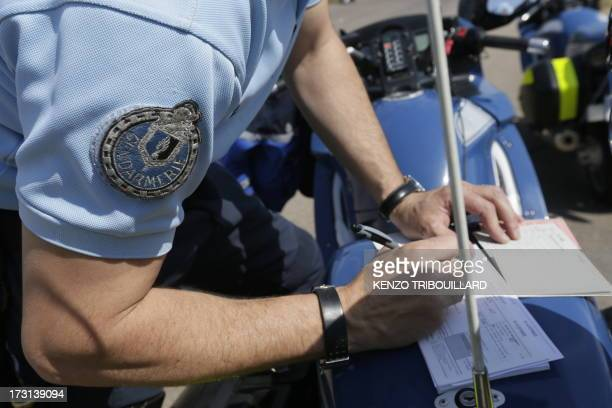 French gendarme Motorcyclist arrests a driver on July 6 on the highway A6-A31 in Beaune, eastern France on the first day of major departures for the...