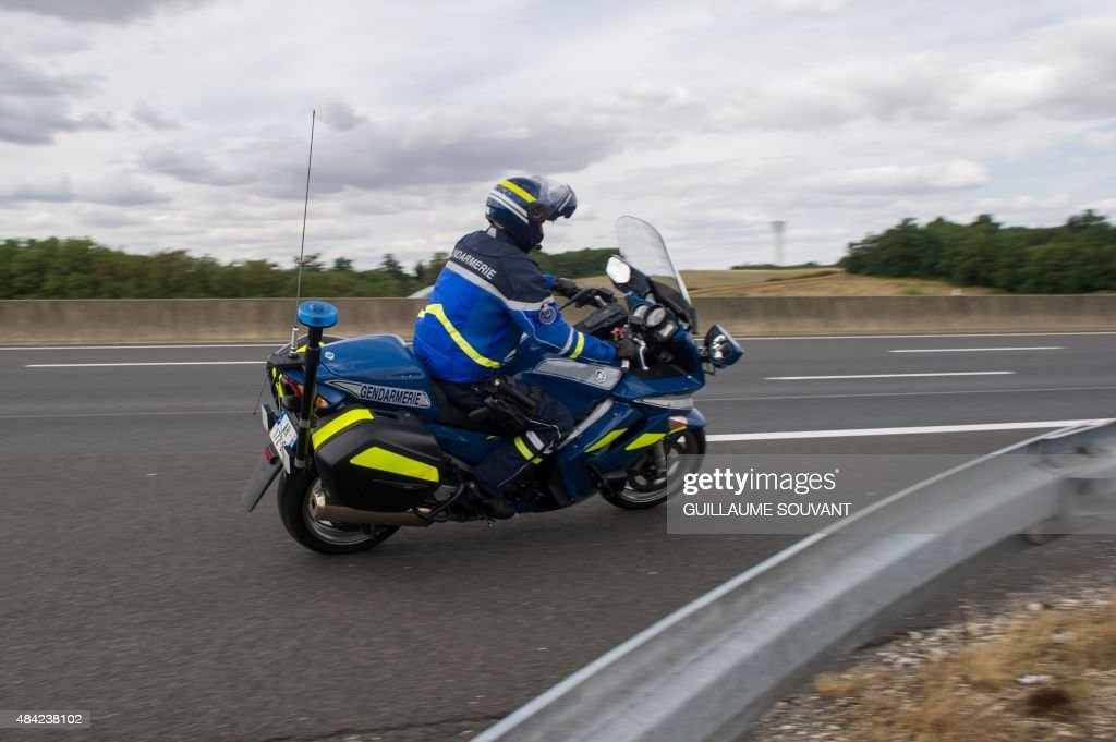 A French Gendarme on a motorbike prepares to intercept a car on August 16, 2015, near the tollgate of Monnaie on the A10 highway. French policemen will reinforce road checks during this weekend of holidays, as drivers are on the road.