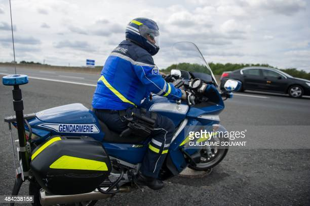 A French Gendarme on a motorbike prepares to intercept a car on August 16 near the tollgate of Monnaie on the A10 highway French policemen will...