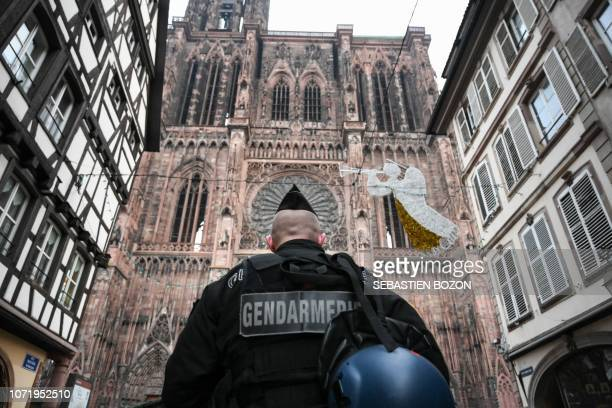 French gendarme patrols in front of the Strasbourg cathedral while searches are conducted on December 12 2018 for the gunman who opened fire near a...