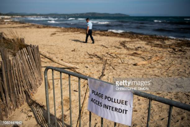 """French gendarme patrols on a beach polluted by hydrocarbon slabs from oil spill near a sign reading """"polluted beach, forbidden access"""" on Pampelone..."""