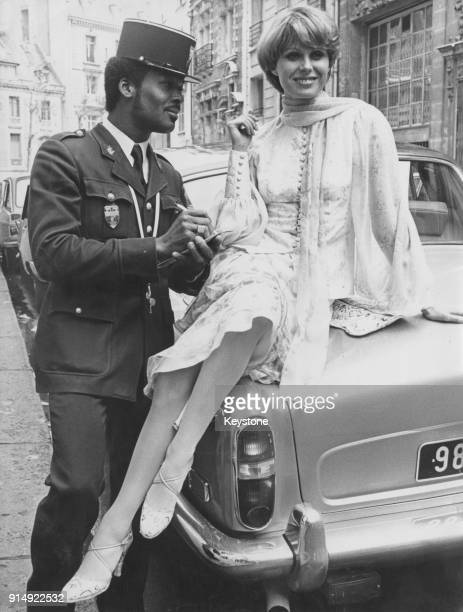 A French gendarme requests an autograph from English actress Joanna Lumley during her visit to Paris France to publicise her upcoming part in...