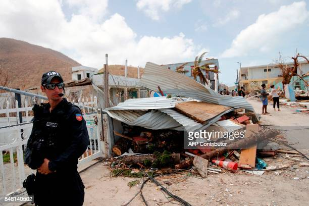 A French gendarme stands besides the wreckage of destroyed buildings on the French island of Saint Martin during the visit of French President...