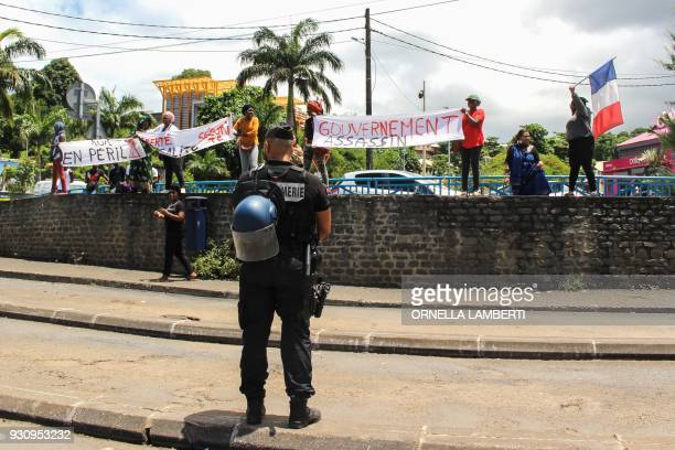 A French gendarme stands guard as protesters hold banners during the arrival of the French Overseas Minister on March 12 2018 in Mamoudzou on the...