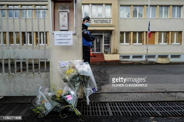 French Gendarme stands guard next to flowers laid at the entrance of the Gendarmerie in Ambert, central France on December 23 after three gendarmes...