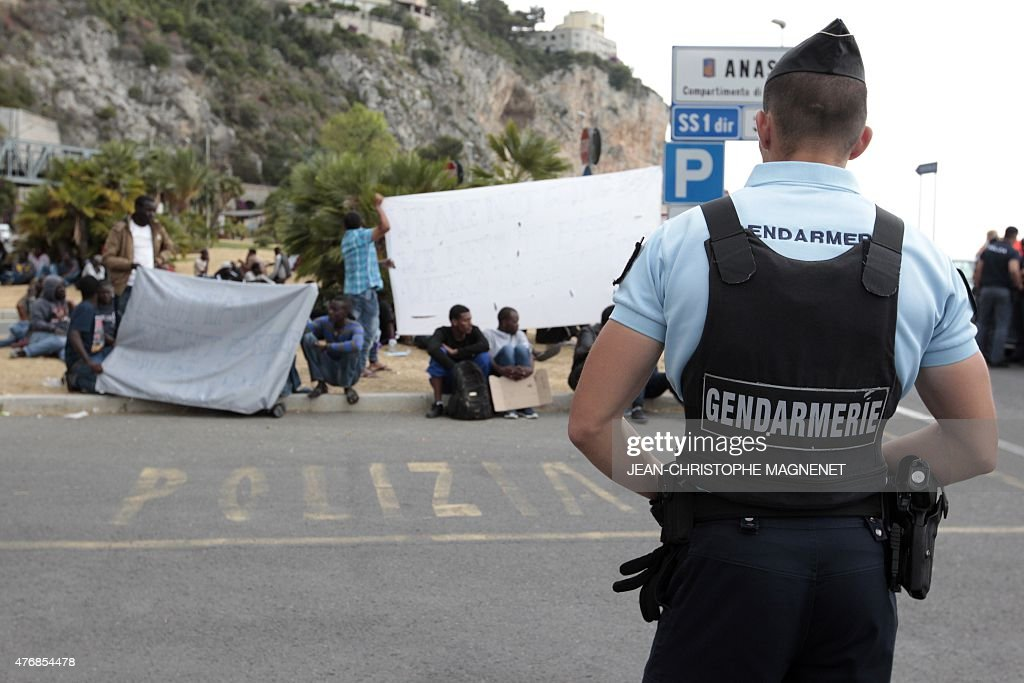 A French Gendarme (Front) Stands Guard On The French Side Of The  French Italian Border In Menton, As Migrants (Rear) Hoping To Cross Wait On  The Italian ...