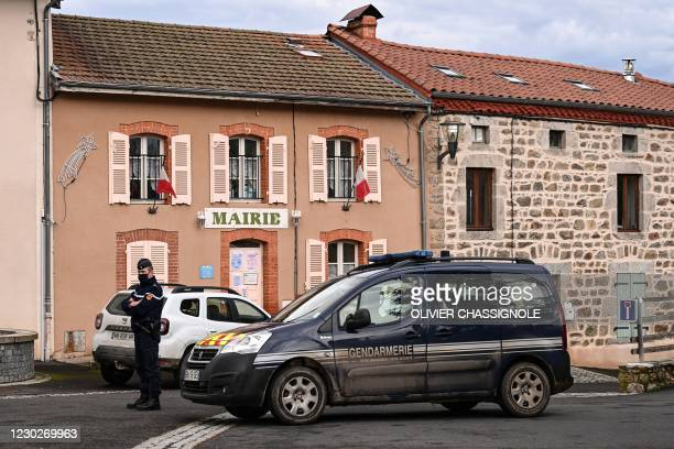 French Gendarme stands in front of the city hall in Saint-Just, central France on December 23 after three gendarmes were killed and a fourth wounded...