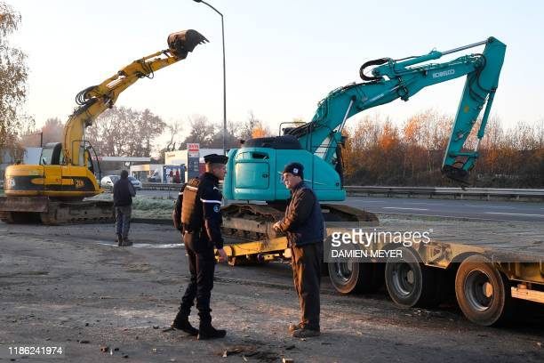 French gendarme stands next to public works company truck and excavator after clearing access to a fuel depot in Vern-sur-Seiche, near Rennes,...