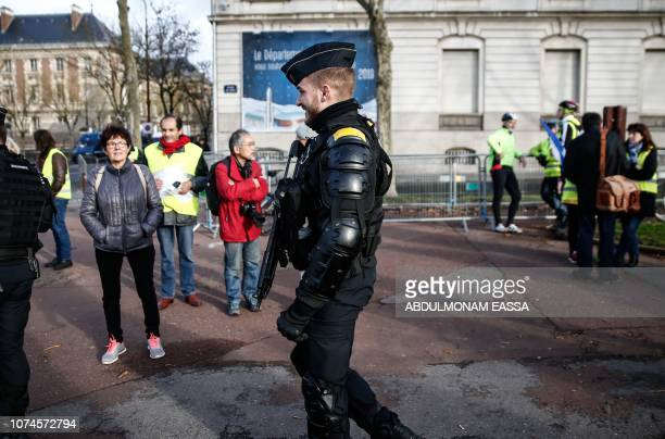 A French gendarme walks next to protesters wearing 'Yellow Vest' in a street in Versailles outside Paris on December 22 2018 The 'Yellow Vests'...