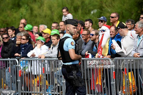 French Gendarmerie officer stand guard as fans gather near the start line prior to the 188 km first stage of the 103rd edition of the Tour de France...