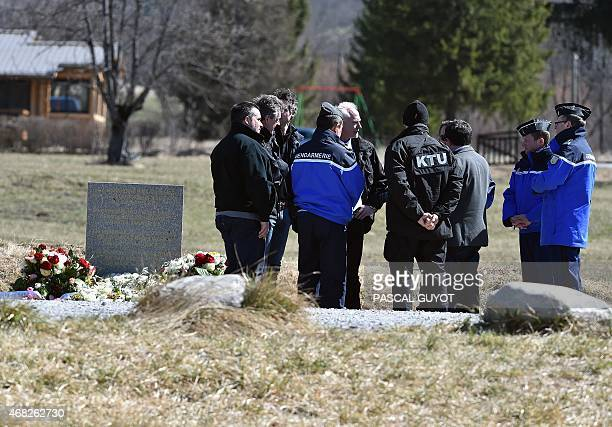 French gendarmes and German police officers stand on April 1 2015 near a stela commemorating the victims of the March 24 Germanwings Airbus A320...
