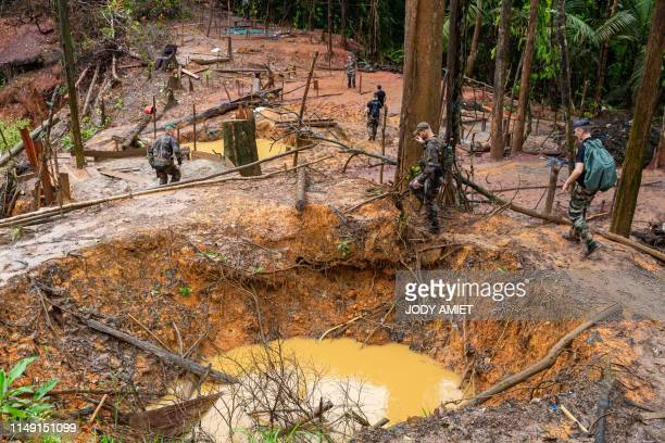 TOPSHOT French gendarmes and members of the World Wildlife Fund arrive on an illegal gold panning site near the village of Cacao 60 kms from the...