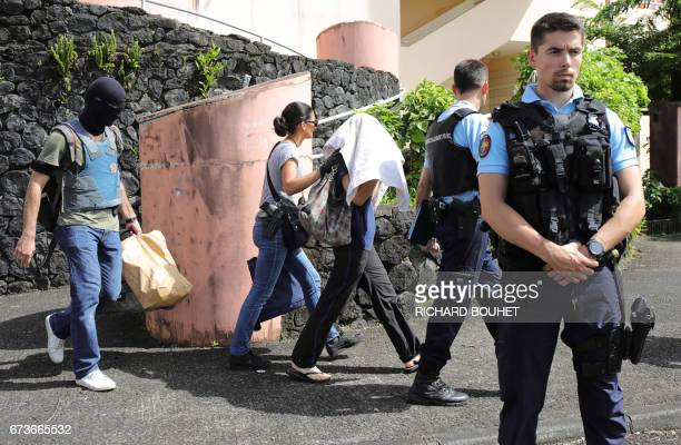 French gendarmes and police officers escort a person on April 27 2017 in SaintDenisdelaReunion on the French Indian Ocean island of Reunion after a...