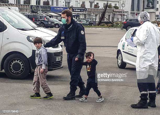 French Gendarmes and police, wearing protective masks against the noverl coronavirus, COVID-19, assist migrants, including five children and a baby,...