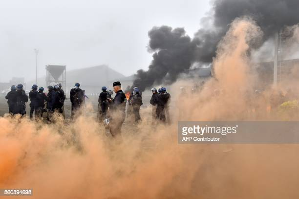 TOPSHOT French gendarmes are surrounded by smoke as they face dockers demonstrating against the labour law reform and the ecologic transition on the...