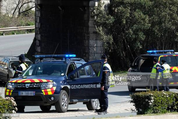 French gendarmes block an access to Trebes where a man took hostages at a supermarket on March 23 2018 in Trebes southwest France At least two people...
