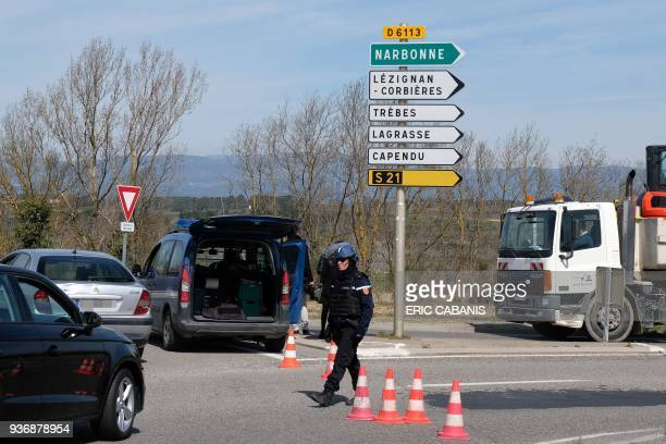 TOPSHOT French gendarmes block the access to Trebes where a man took hostages at a supermarket on March 23 2018 in Trebes southwest France At least...
