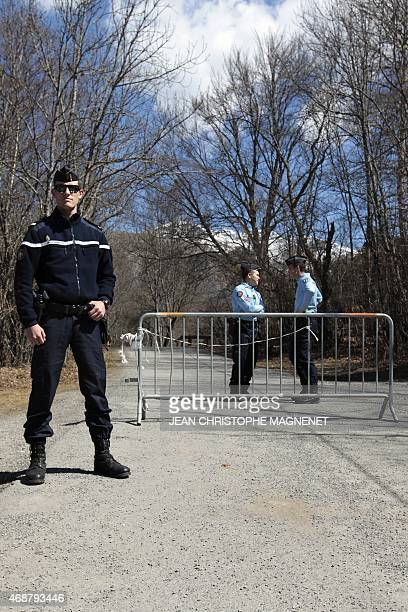French gendarmes block the road leading to the site of the Germanwings Airbus A320 crash in the village of Le Vernet French Alps on April 7 2015 A...