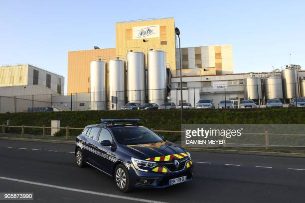 French gendarmes drive by the Celia dairy company's infant milk factory a subsidiary of French dairy giant Lactalis in Craon western France on...