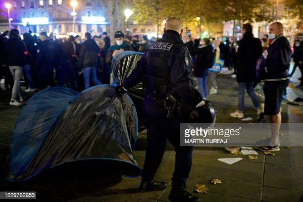 French gendarmes evacuate a makeshift tent camp set up by migrants, officials and ONG volunteers on Republique square in Paris on November 23 one...