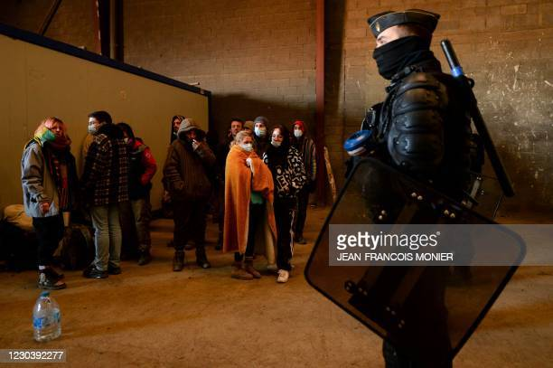 French Gendarmes evacuate the last partygoers who attended a rave in a disused hangar in Lieuron about 40km south of Rennes, on January 2, 2021. -...