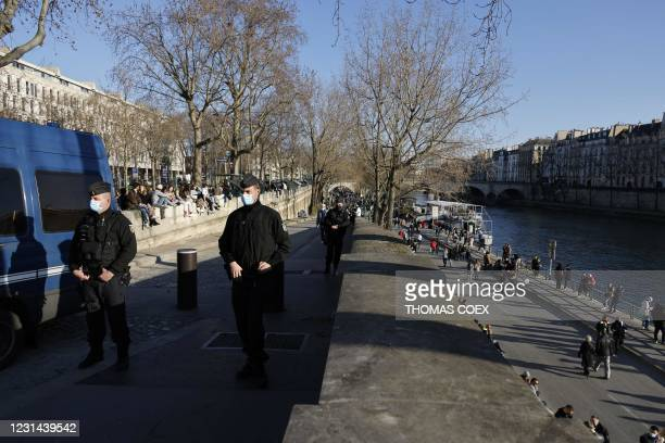 French gendarmes filter and forbid people to go down on the quays along the River Seine, in Paris, on February 28, 2021. - A wall of scepticism on...