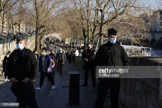 French gendarmes filter and forbid people to walk down on the quays along the River Seine, in Paris, on February 28, 2021. - A wall of scepticism on...