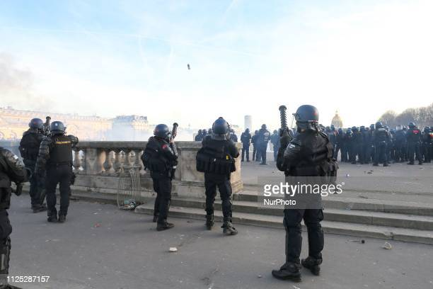 French gendarmes fire smoke grenades from gas guns during a Yellow vest antigovernment demonstration on February 16 2019 in Paris on Esplanade des...
