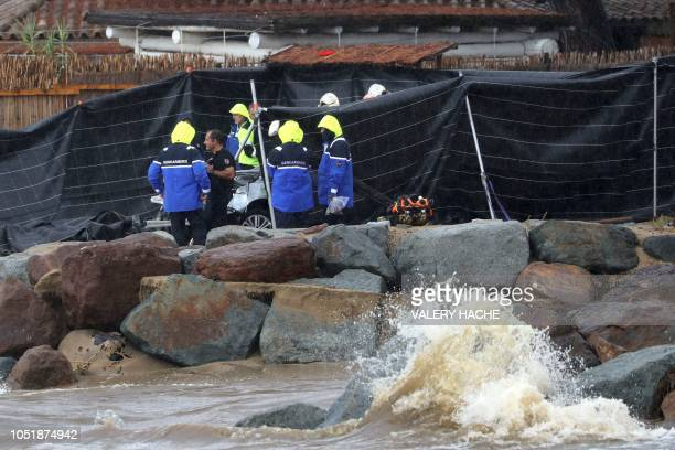 French gendarmes investigate on October 11, 2018 in Sainte-Maxime, on the site where a body was found in a car washed into the sea overnight after...