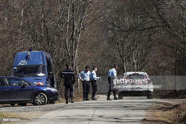 French gendarmes let a car pass as they block the road leading to the site of the Germanwings Airbus A320 crash in the village of Le Vernet French...