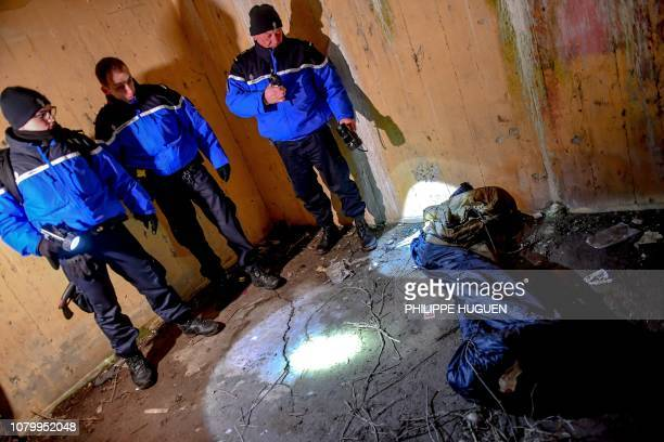 French gendarmes look at a sleeping bag in a bunker as they patrol on the beach of Oye-Plage, near Calais, northern France, on January 9, 2019 to try...