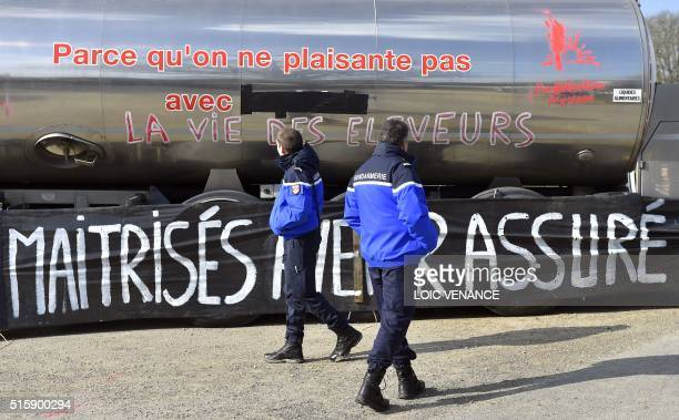 French gendarmes look at a tanker truck carrying milk from dairy product corporation Lactalis as it is blocked on a road in Vay western France on...