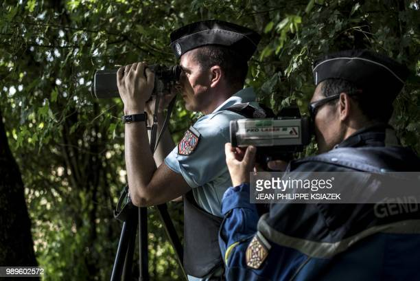 French gendarmes look through speed cameras during an educational speed control on a secondary road with a newly imposed speed limit of 80 kmph, on...