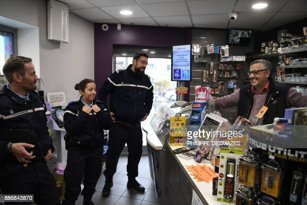 French gendarmes of the Territorial Contact Brigade speak with a tobacconist as they patrol on November 27 2017 in Lhuis eastern France / AFP PHOTO /...