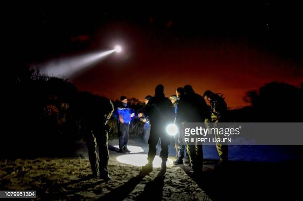 French gendarmes patrol while a police helicopter fly over the beach of Oye-Plage, near Calais, northern France, on January 9, 2019 as they try to...