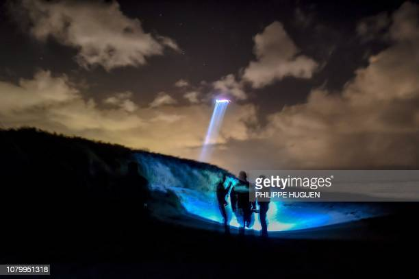 TOPSHOT French gendarmes patrol while a police helicopter fly over the beach of OyePlage near Calais northern France on January 9 2019 as they try to...