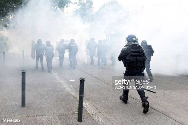 French gendarmes run through the tear gas smoke at the Breil neighbourhood in Nantes on July 4 2018 Groups of young people clashed with police in...