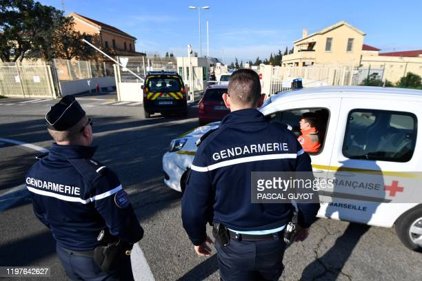 French gendarmes stadn guard as gendarmerie and French Red Cross vehicles arrive at the Istres-Le Tube Air Base near Istres, northwest of Marseille,...