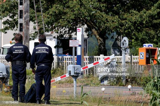 French gendarmes stand at a level crossing on July 15 after a car and a TER regional express train crashed at the exit of the train station in...
