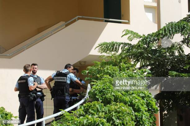 French gendarmes stand at the entrance of a building on April 27 2017 in SaintDenisdelaReunion on the French Indian Ocean island of Reunion after a...