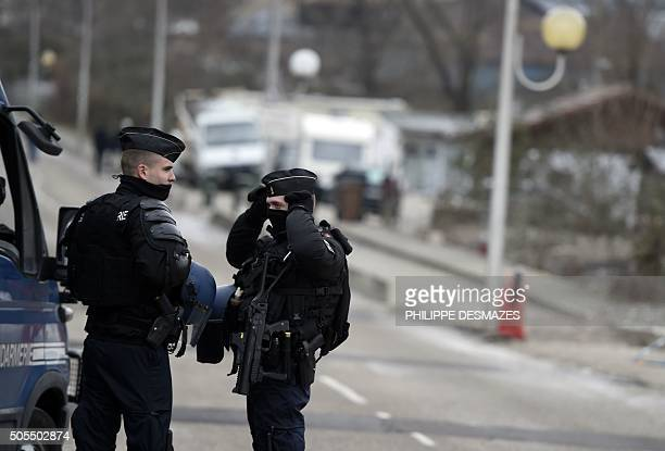 French gendarmes stand guard in front of the traveller community camp on January 18 2016 in Moirans after a police operation early this morning to...