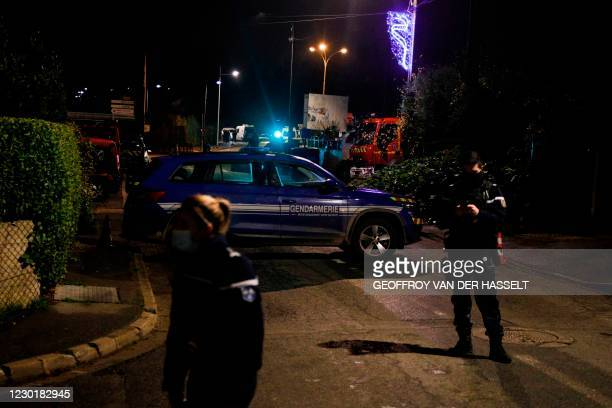 French gendarmes stand guard next to a car as the road is blocked on December 17, 2020 in Domont, north of Paris where an armed man is entrenched...