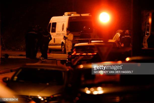 French gendarmes stand guard next to cars as the road is blocked on December 17, 2020 in Domont, north of Paris where an armed man entrenched with...