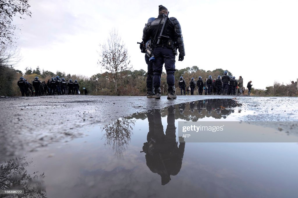French gendarmes stand near a protest of opponents to the project of an international airport in Notre-Dame-des-Landes during a protest, on December 15, 2012, in Notre-Dame-des-Landes, western France. French court ordered on December 12, 2012 the expulsion of the opponents to the airport that is supposed to open in 2017.